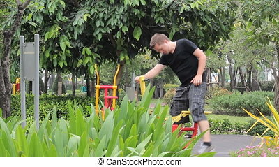 Young Adult Working Out At The Park - A young man begins...