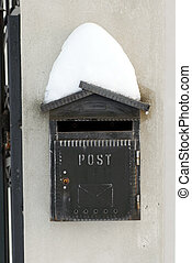 Snow on mail post box - vintage black mail box covered by...