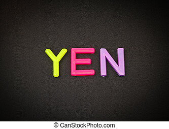 Yen in colorful toy letters on black background