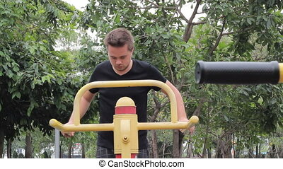 Man Exercising In The Park - A young man begins working out...