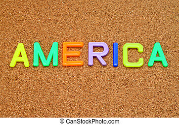 America in colorful toy letters on cork background