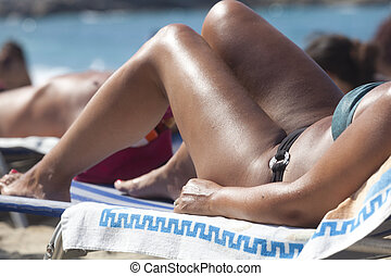 Woman in bikini laying on the beach - Young sexy woman in...