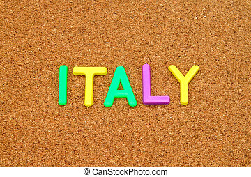 Italy in colorful toy letters on cork background
