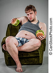 fat man eating hamburger seated on armchair