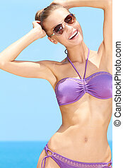Pretty female with sunglasses on at the pool