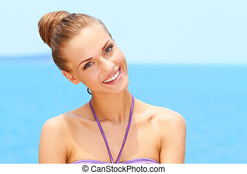 Portrait of charming young woman smiling at beach