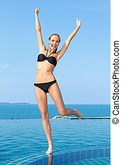 Fun at the pool - Portrait of carefree woman having fun with...