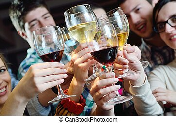 Group of happy young people drink wine at party disco...