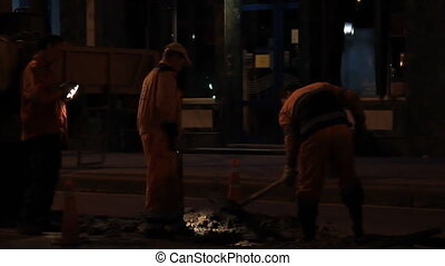 Road workers by night street