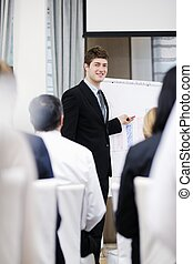 Young business man giving a presentation on conference -...