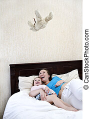 Mom and daughter having fun with a flying teddy bear toy