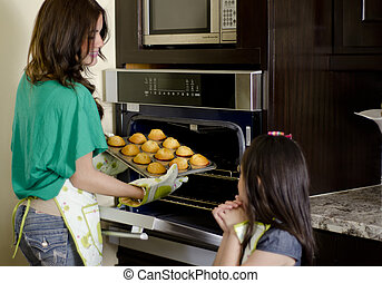Mom and daughter baking cupcakes