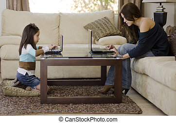 Mom and daughter using laptops