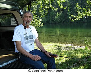 Old man smoking pipe - Senior relaxing by the riverside