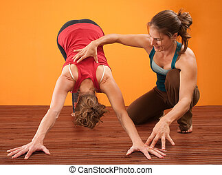 Helping With Yoga - Yoga teacher helps student perform Adho...