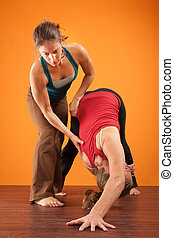 Yoga Partners - Yogasana teacher assisting her student over...
