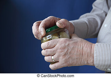 senior man tries to open jar - an older man struggles to...