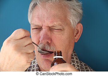 taking bitter medicine - sick man frowns as he takes a...