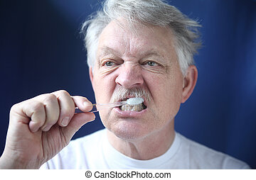 mature man brushes teeth - a senior man brushes his teeth