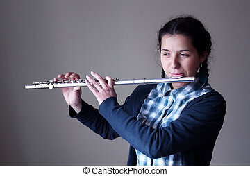 Teenage girl plays the flute