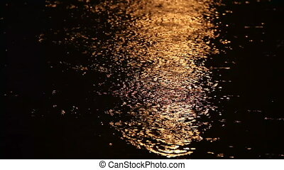 Raindrops reflections on water surface by night