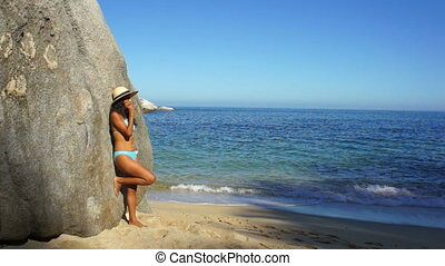 Girl looking at the ocean - Young woman leaning on a rock...