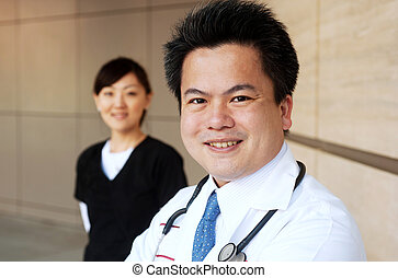 Asian doctor with nurse in background standing outside