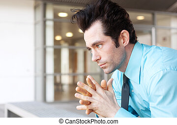 Frustrated businessman sitting on a bench, deep in thought