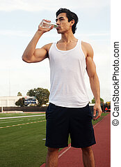 Young male latino athlete drinking water standing on...