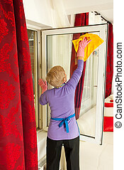Rear view of woman cleaning window - Rear view of senior...