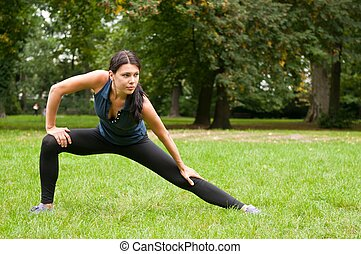 Woman performs stretching before sport in park - Young woman...
