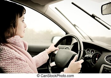 Young woman driving car in rain - Young business woman...