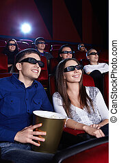 In the cinema - People watch a movie in 3D glasses in the...