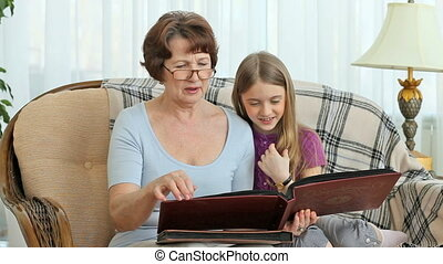 Grandma stories - Grandmother showing granddaughter the...