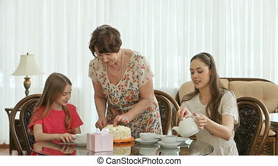 Tea party - Senior woman cutting cake, young woman pouring...