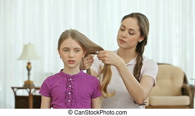 Braiding - Young woman doing girl%u2019s hair