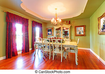 Large green dining room with cherry hardwood.