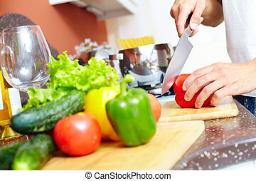 Cutting pepper - Close-up of young man cutting vegetables in...