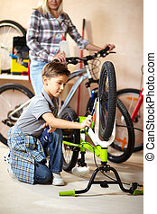Boy working - Portrait of cute boy repairing bicycle wheel...