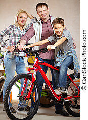Family of bikers - Portrait of happy family with bicycle...