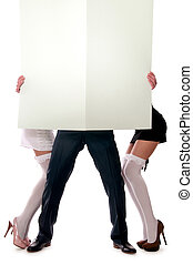 Two women and a man holding a sheet of paper