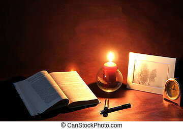 Meditations, exposed book and burning candle