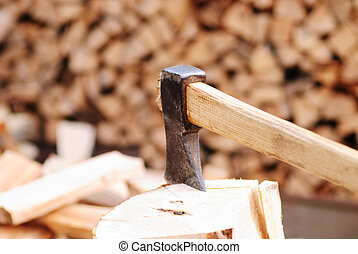 Firewood with axe and male hand. close up, shallow deep of...