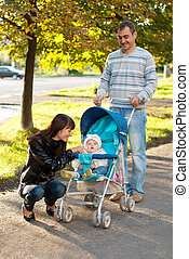 Happy family outdoor with carriage - Happy family outdoor -...