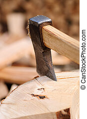 Firewood with axe and male hand close up, shallow deep of...