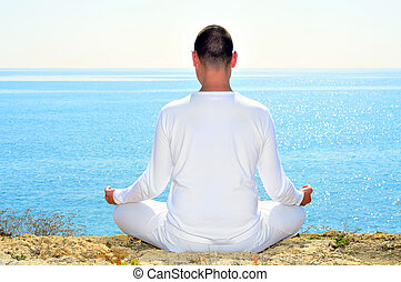 meditation - someone meditating in front of the sea