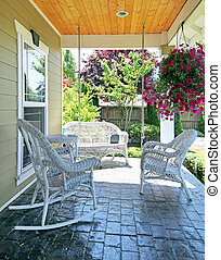 Front porch with white furniture and flowers. - Front porch...