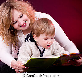 Mother and baby boy reading book and smiling on red...