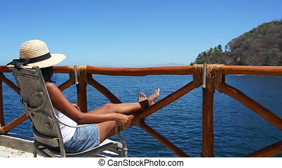 Woman enjoying the view - Young woman sitting on a balcony...