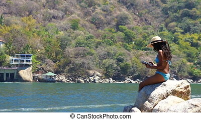 Woman reading a book - Young woman sitting on a rock reading...